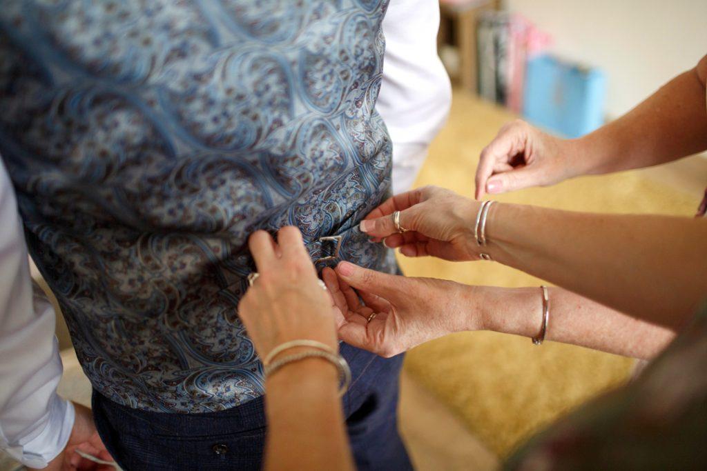 Four arms tying up grooms waist coat - Whiston Manorial Barn Wedding Photography,Rotherham  wedding photographer
