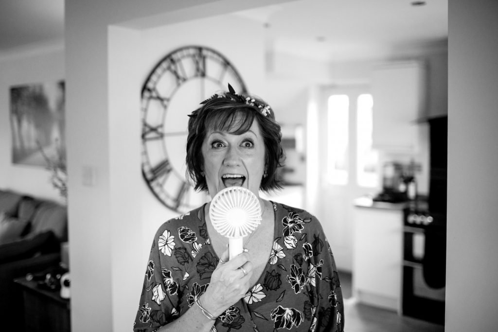 Amanda the bride with her portable fan before her wedding at Whiston Manorial Barn Wedding Photography